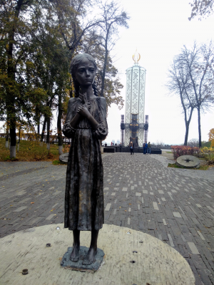 Monument to victims of Holodomor with museum on the background (Kyiv)